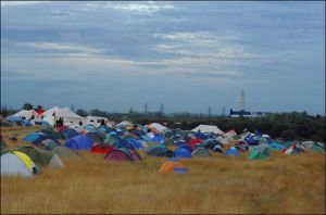 Kingsnorth Coal Fired Power Plant Looms in the background as tents of resistence spring up all around